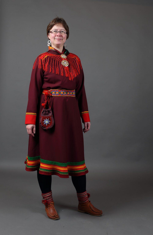 Kvinne i mørkerød Lyngenkofte, med silkesjal, kåkesølvbelte, to søljer i halsen, veske og komager med komagband