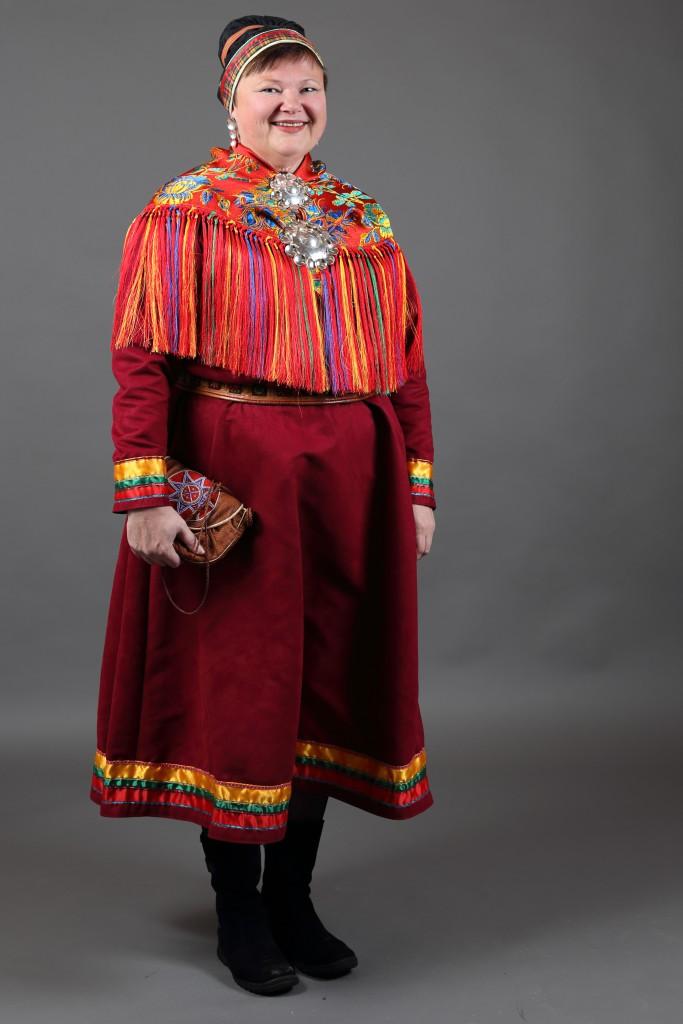Kvinne med mørkerød Lyngenkofte, silkesjal og gobbagahpir på hodet.