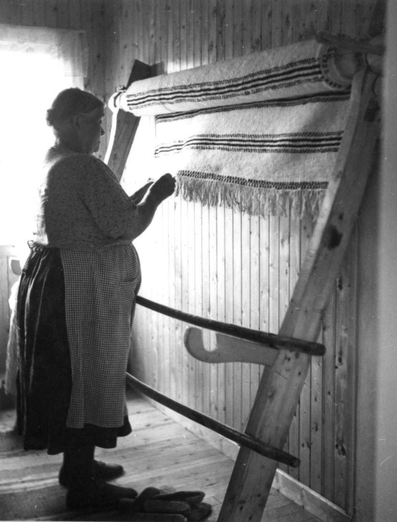 Ane Hansen Blomsterli, født på Oppervoll, vever grene (1955). Fotograf: Marta Hoffmann, Norsk Folkemuseum. Eldre kvinne med skaut og forkle som står foran veven og er ferdig med en grene.