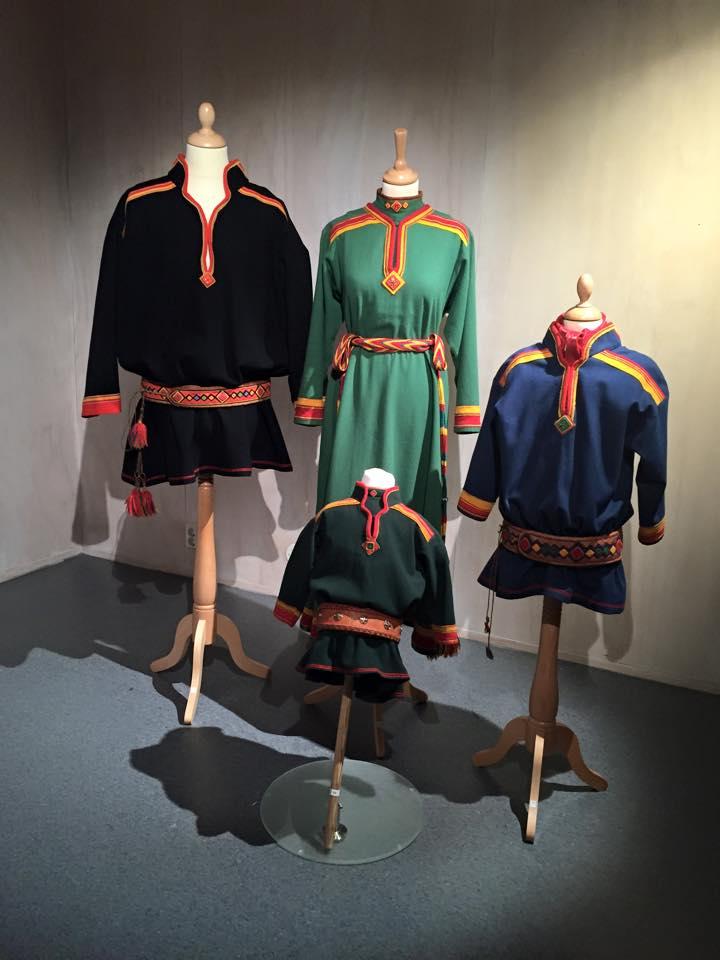 Bilde fra utstilling, fire kofter. Svart herrekofte, grønn damekofte, en blå og en mørkegrønn guttekofte. Alle med belte.
