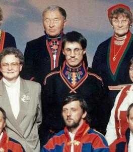 Utsnitt av gruppebilde av det første Sametinget 1989, der vi ser Lars Nilsen Marakatt i den første Lyngenkofta. Den er svart, med blå brystduk som har grønn, rød og blå pynt og kråkesølv.