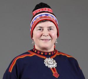 Nærbilde av kvinne med gobbagahpir. Hun har blått bomullstøy, rødt bånd og hvitt bånd nederst på luen. Luebåndet hennes er vevd.