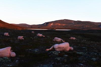 Åtte nakne menn ligger på siden i mørkt lansdskap. Fjell og blå himmel i bakgrunnen. Foto av Gjert Rognli.