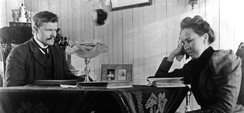Anders LArsen sitter vedet bord med en dame som leser.
