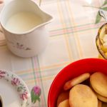 KJøkkenbord med småkaker, skål med sukkerbiter, kopp med kaffe, skål med melk.