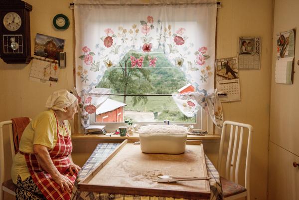 Oliva sitter ved kjøkkenbord og titter ut av vindu. På bordet brøddeig til heving.