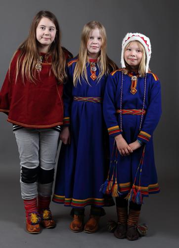 En jente med luhkka og to jenter i kofte.