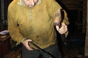 Hans bearbeider knivbladet på ambolten.