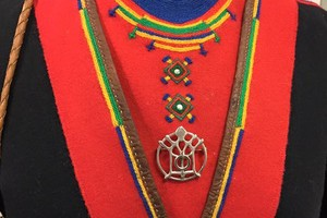 Nærbilde av koftebryst. Rød og svart, med pynt i grønt, gult og blått. Kråkesølvapplikasjoner og sølvbrosje.