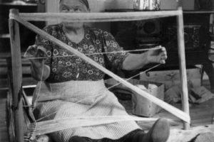 Kvinne som sitter på gulvet og bruker den tradisjonelle renningstolen og grindvev for å lage jarekanten til greneveven