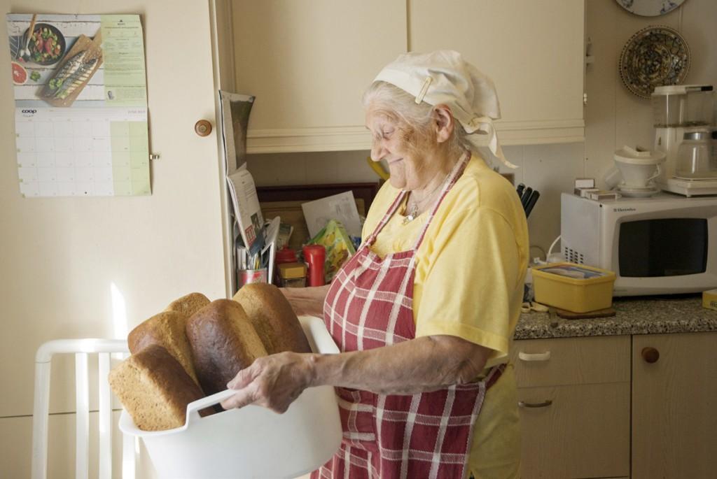 Oliva Nilsen bærer på balje med nybakte brød.