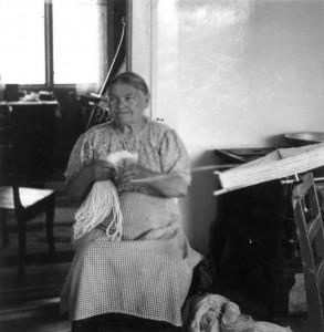 Eldre dame, Anne H. Blomsterli sitter på en stol og lager innslagsdukker/uddu til greneveven.