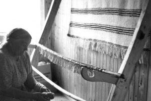 Anne H. Blomsterli klipper grenen løs fra veven. Foto: Marta Hoffmann, Norsk Folkemuseum