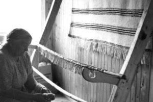 Eldre kvinne sitter ved siden av veven og nøster tråder. Grenen er klippet løs nederst og henger ned fra veven.