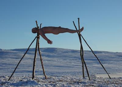 Naken mann båret på stokker i nakent landskap. Foto av Gjert Rognli.