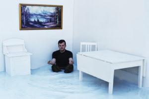 Sortkledd mann sitter i et hjørne i et hvitt rom, hvite bord og skap, naturmaleri på veggen.