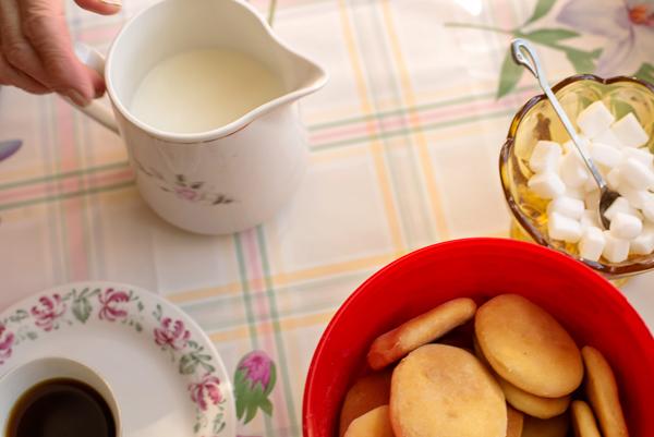 KJøkkenbord med kjeks, skål med sukkerbiter, kopp med kaffe, skål med melk.