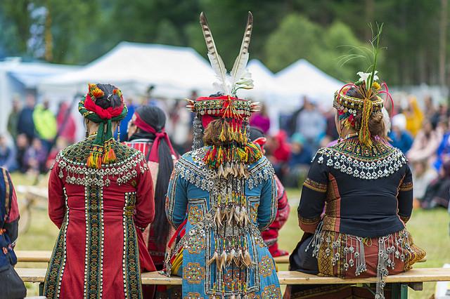 Tre damer i tradisjonelle kostymer sitter på benk med ryggen til. Foto: Ørjan Bertelsen.