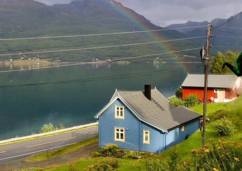 Regnbue over blått hus i kulturlandskap Skardalen