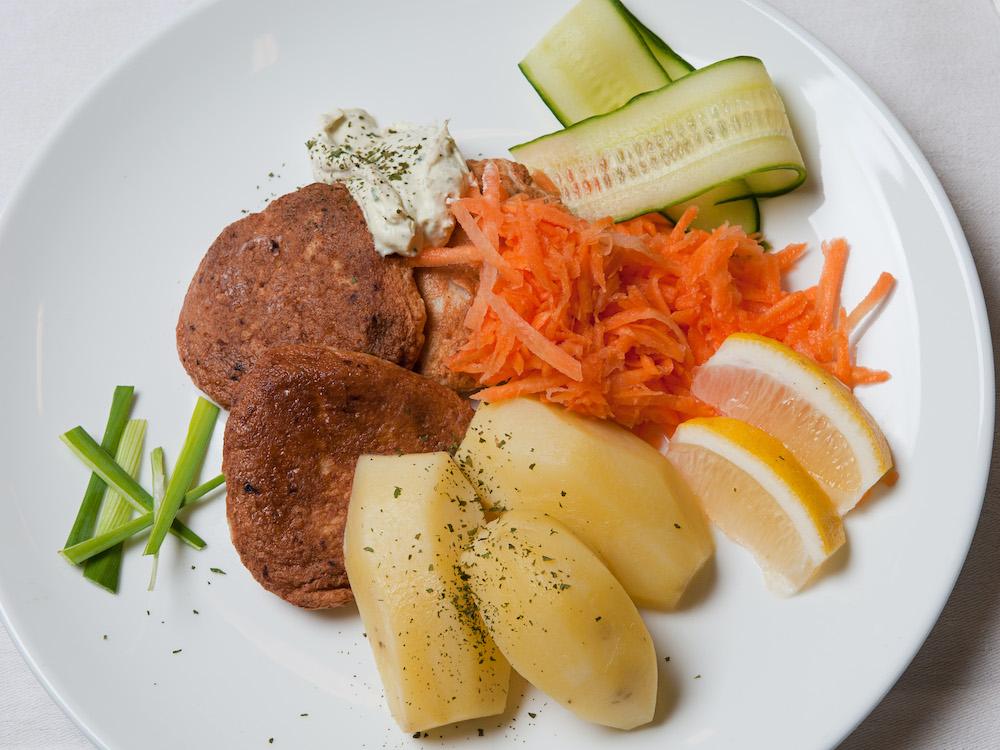 Fiskekaker med råkost, agurk, poteter og dressing.